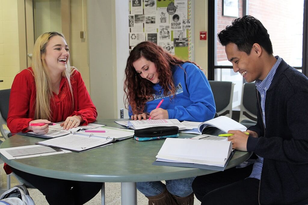 Three students laughing while studying