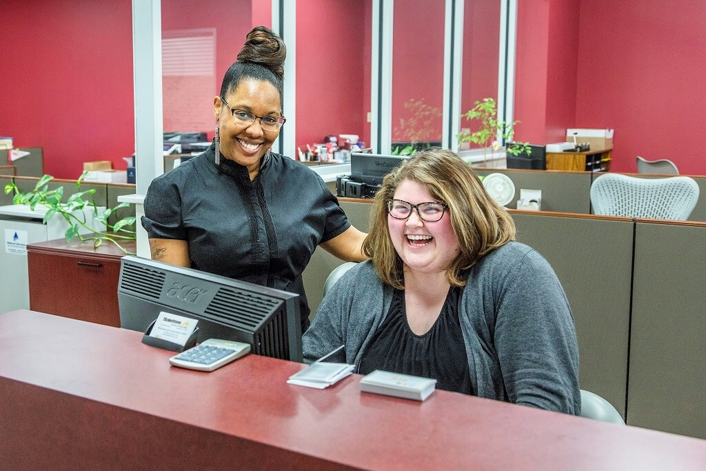 Two women smiling at the camera from behind a receptionist desk