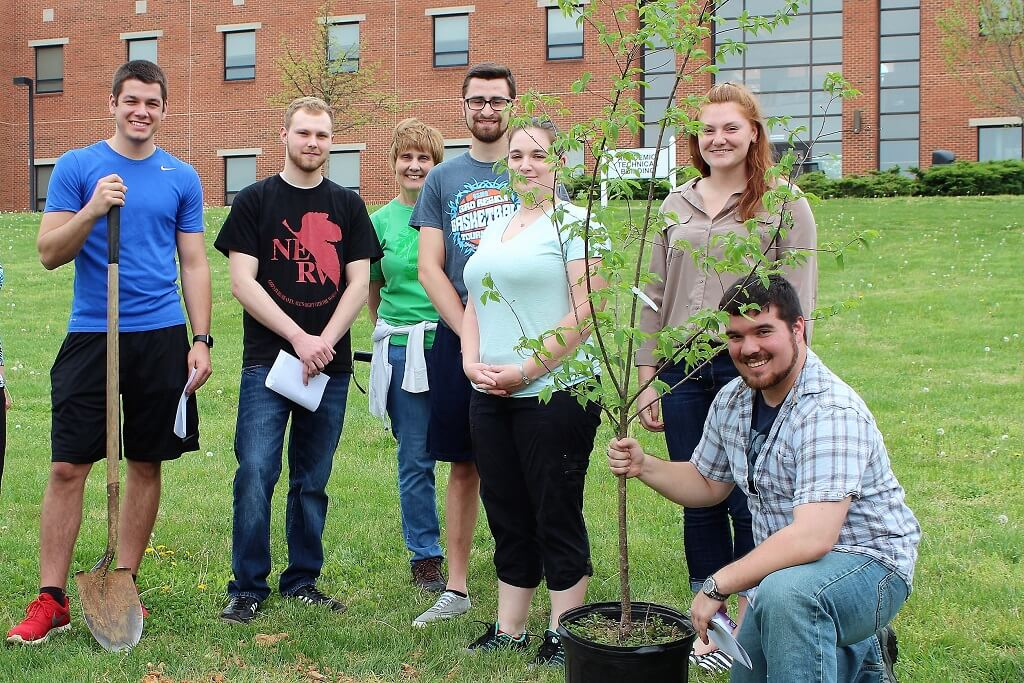 Seven students posing with two newly planted trees