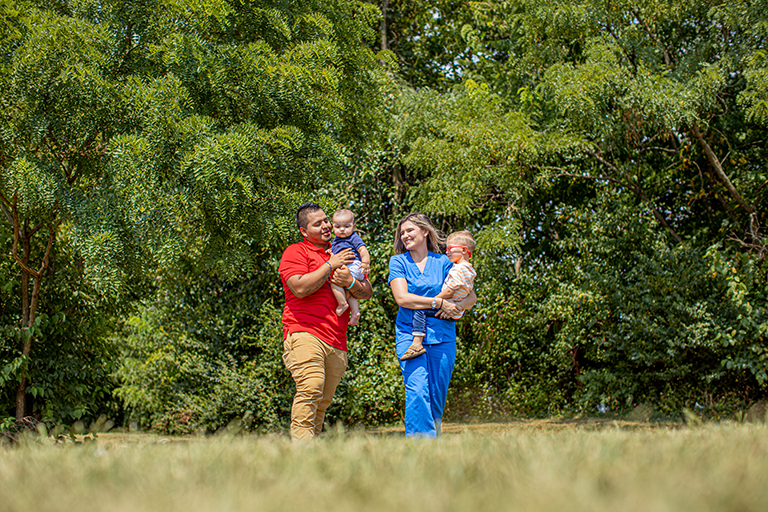 Man and woman in nurse scrubs carrying kids through a field