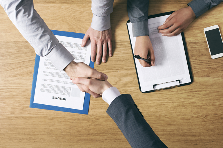 handshake during interview with resume and contract agreement on table