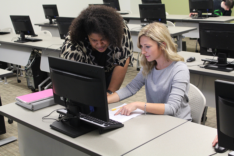 A woman instructor assisting a student in a computer lab