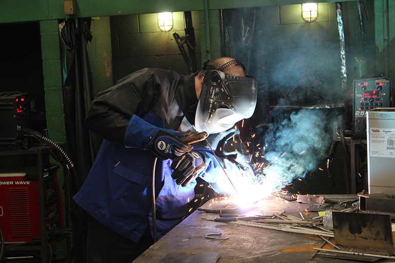 A male student welding metal materials